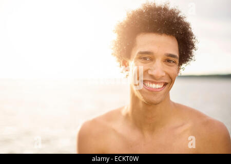 Portrait of happy young man against lake - Stock Photo