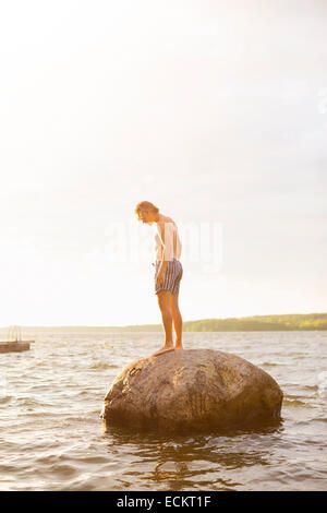 Full length side view of man standing on rock in lake against sky - Stock Photo