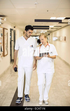 Full length of doctors discussing over digital tablet in hospital corridor - Stock Photo