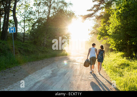 Full length rear view of couple walking on dirt road - Stock Photo