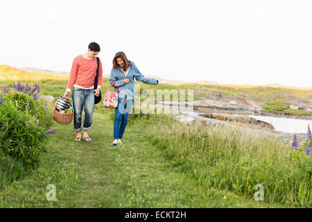 Full length front view of couple walking on field - Stock Photo
