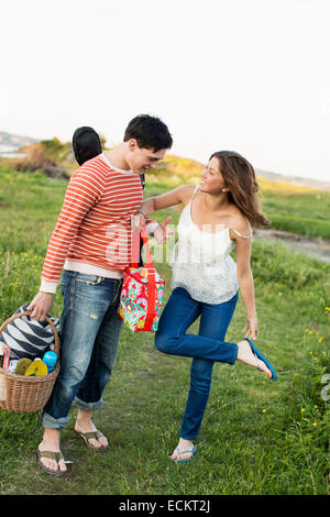 Full length of couple standing on field - Stock Photo
