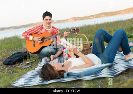 Teenage girl reading book with boyfriend playing guitar during picnic - Stock Photo