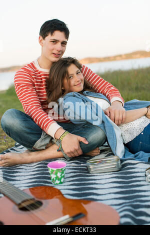 Portrait of smiling couple enjoying picnic in field - Stock Photo