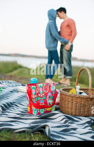 Picnic basket and bag on blanket with loving couple at background - Stock Photo