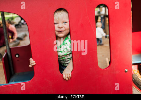 Portrait of happy baby boy peeking through red playing equipment in park - Stock Photo