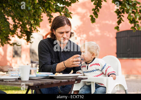 Father feeding water to baby girl in park - Stock Photo