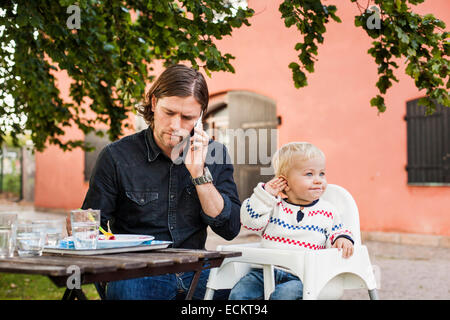 Young man using mobile phone while feeding baby girl in park - Stock Photo