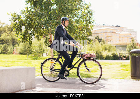 Full length of businessman riding bicycle in park - Stock Photo