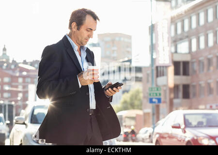 Businessman using mobile phone and holding disposable coffee cup while walking on city street - Stock Photo