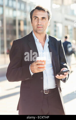 Businessman looking away while holding mobile phone and disposable coffee cup on city street - Stock Photo