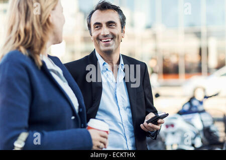 Happy businessman talking to female colleague outdoors - Stock Photo