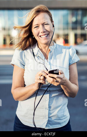 Portrait of happy businesswoman using mobile phone outdoors - Stock Photo