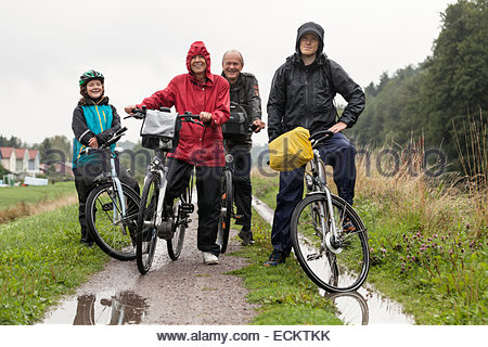 Portrait of happy multi-generation family with bicycles on field against clear sky - Stock Photo