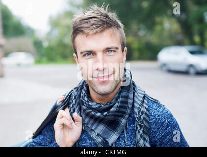 Portrait of smiling young man on street - Stock Photo