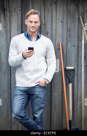 Portrait of mature man using smart phone against wooden wall - Stock Photo