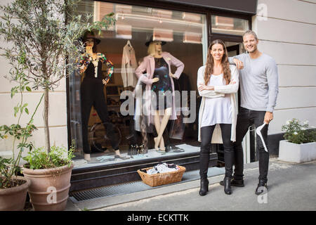 Portrait of smiling owner with female worker standing in front of clothing store - Stock Photo