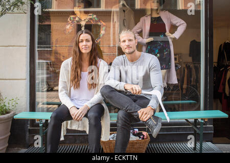 Portrait of owner with female worker sitting in front of clothing store - Stock Photo