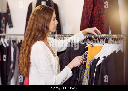 Female sales person arranging cloths in clothing store - Stock Photo