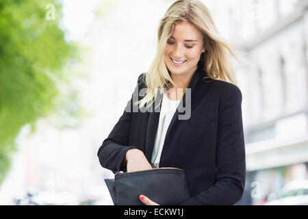 Smiling young woman searching something in her clutch bag outdoors - Stock Photo
