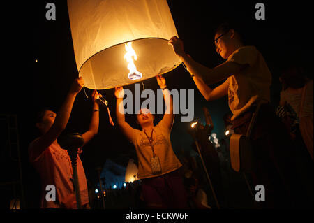 CHIANG MAI, THAILAND - OCTOBER 25, 2014: Group of young Thai people launch a sky lantern on the night of the Yee - Stock Photo
