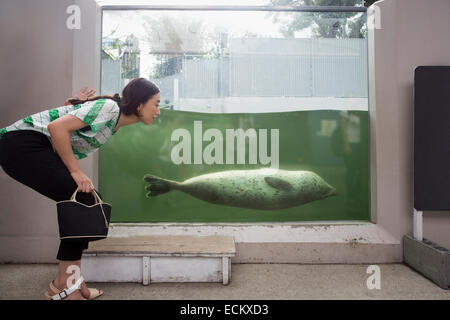 A woman crouching by a marine tank at an aquarium exhibit.  An animal in the water. - Stock Photo