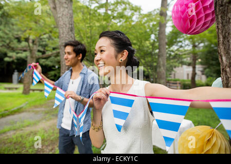 Group of people hanging lanterns and flags on trees in a wood. - Stock Photo