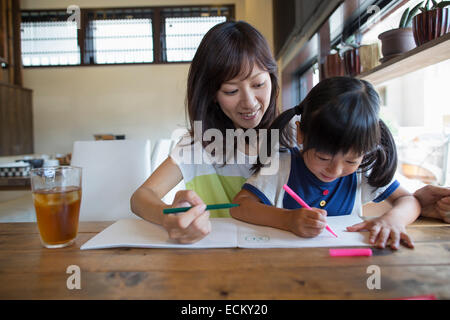 Mother and daughter sitting at a table, drawing with felt tip pens, smiling. - Stock Photo