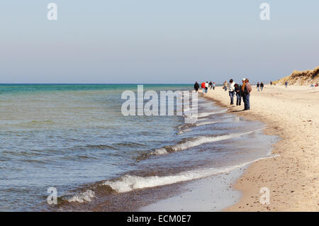 People walking towards the beach of Darsser Ort towards the lighthouse - Stock Photo