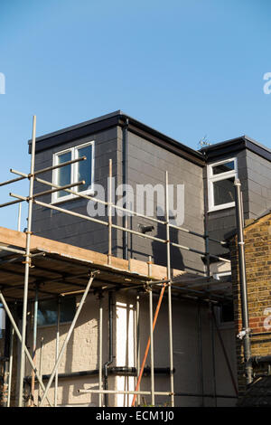 Scaffolding to a newly completed dormer / dormers / dormas / dorm on the roof on a Victorian terraced house in Twickenham. - Stock Photo