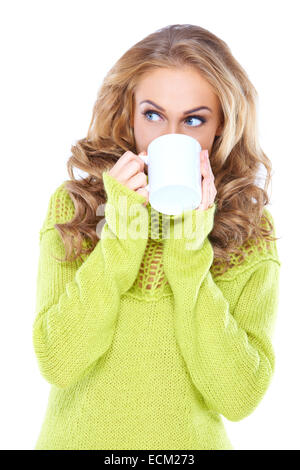 Attractive young blond woman drinking coffee while looking aside watching something on the left of the frame - Stock Photo