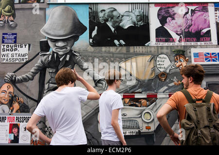Young travelers in front of iconic images at the East Side Gallery on part of the Berlin Wall. - Stock Photo