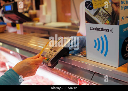 A woman pays on a butchery with a contactless credit card system in the island of Majorca, Spain - Stock Photo