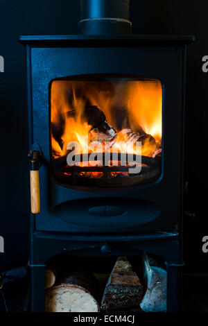 A small cast-iron wood burning stove fire fireplace burning firewood logs with an orange flame - Stock Photo