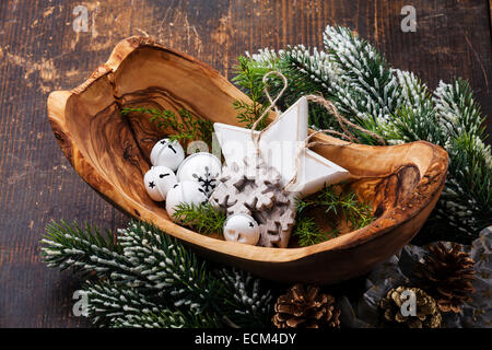 Christmas decorations Bells in olive wood bowl on green fir branches background - Stock Photo