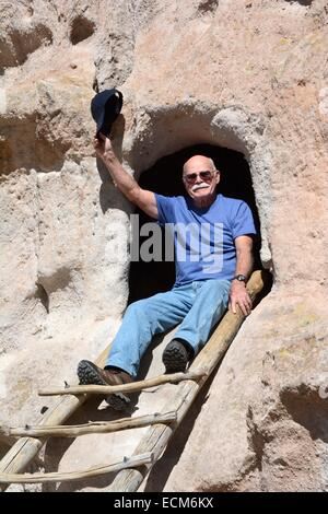 80 year old brother at top of a ladder leading into a room carved out of rock by the Anasazi Indians over 10,000 - Stock Photo