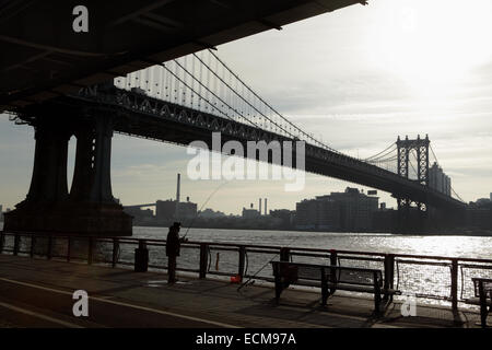 Man fishing from the East River Esplanade in New York City as the sun rises over the Manhattan Bridge - Stock Photo