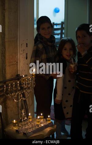 (141217) -- JERUSALEM, Dec. 17, 2014 (Xinhua) -- Ultra-Orthodox Jewish children stand by a lit Hannukiya at their - Stock Photo