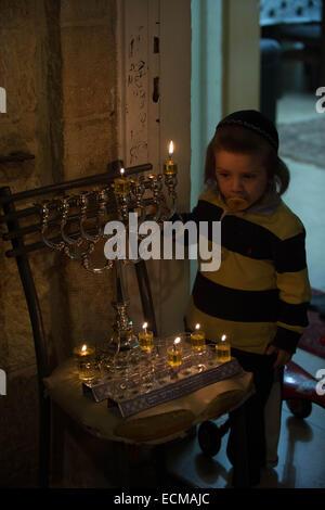 (141217) -- JERUSALEM, Dec. 17, 2014 (Xinhua) -- An Ultra-Orthodox Jewish boy watches a lit Hannukiya at his home - Stock Photo