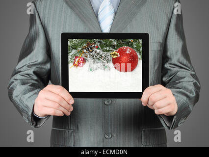 Man holds tablet PC with Christmas composition on dark background - Stock Photo