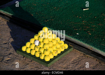 Tropical golf driving range with golf balls stacked in pyramids. - Stock Photo