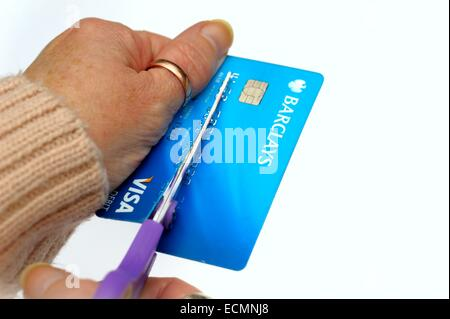 A woman cutting up a visa debit card on a white studio background England UK - Stock Photo