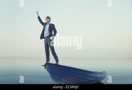 Cheerful young guy on the tiny boat - Stock Photo
