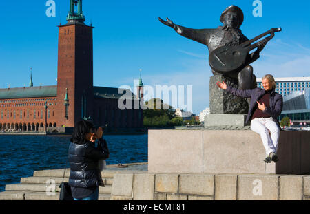 Stockholm Sweden downtown City Hall and women tourists on Music statue near water in city Stadshuset at Lake Malaren - Stock Photo