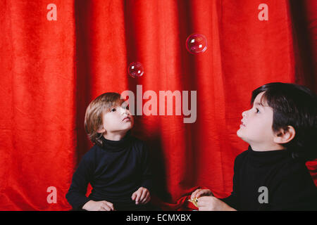 Two boys wearing black clothes playing with soup bubbles on a set - Stock Photo