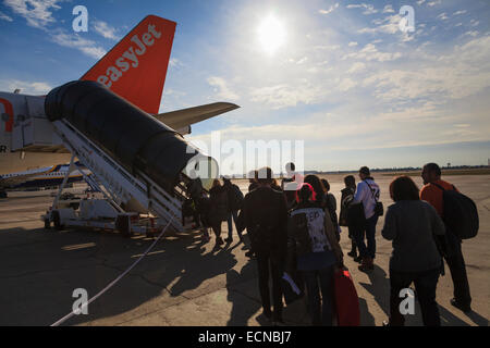 Passengers using the rear aircraft stairs to board an Easyjet aircraft with sunburst - Stock Photo