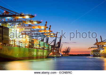 Cargo ships being loaded at Eurokai and Burchardkai in Hamburg Harbor at night, Waltershofer Hafen, Hamburg, Germany - Stock Photo
