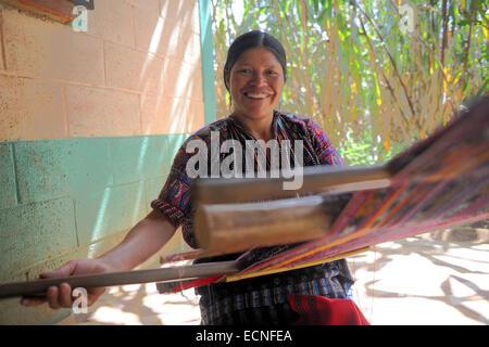 A maya indigenous woman weaves on backstrap loom in Churacruz, Solola, Guatemala. - Stock Photo