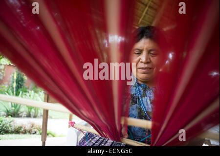 A maya indigenous woman weaves on backstrap loom in Panajachel, Solola, Guatemala. - Stock Photo