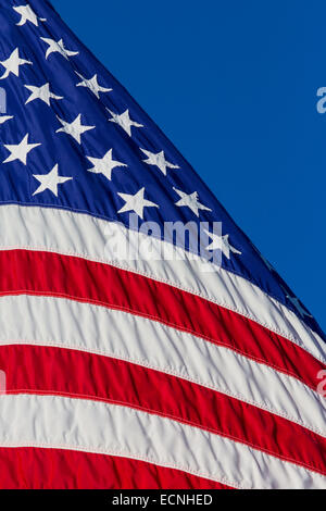 Closeup of portion of American flag against blue sky - Stock Photo